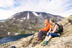 Couples de sport augmentant sur Besseggen Les randonneurs apprécient le beau lac et le temps beau en Norvège Images stock