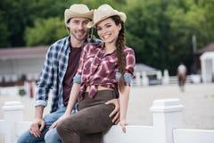 Couples de style de cowboy embrassant et regardant l'appareil-photo tout en se reposant sur la barrière Image stock