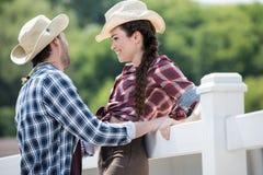 Couples de style de cowboy parlant près de la barrière à la journée Images libres de droits