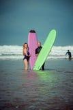 Couples de surfer sur la plage avec un conseil surfant Photographie stock libre de droits