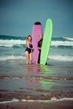 Couples de surfer sur la plage avec un conseil surfant Photographie stock