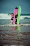 Couples de surfer sur la plage avec un conseil surfant Image libre de droits
