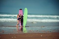 Couples de surfer sur la plage avec un conseil surfant Photos libres de droits