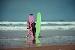 Couples de surfer sur la plage avec un conseil surfant Image stock