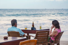 Couples de touristes ayant la boisson à la barre de plage Photo stock
