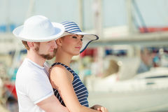 Couples de touristes dans la marina contre des yachts dans le port Images stock