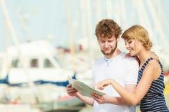 Couples de touristes dans la marina recherchant des directions sur la carte Images stock