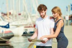 Couples de touristes dans la marina recherchant des directions sur la carte Photos stock
