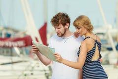 Couples de touristes dans la marina recherchant des directions sur la carte Image libre de droits