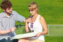 Couples de touristes dans la ville recherchant des directions sur la carte Photo libre de droits