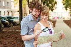 Couples de touristes dans la ville recherchant des directions sur la carte Photographie stock libre de droits