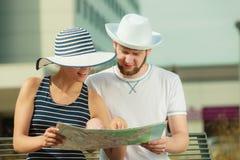 Couples de touristes dans la ville recherchant des directions sur la carte Photographie stock