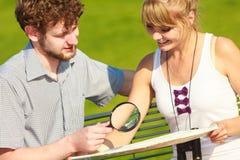 Couples de touristes dans la ville recherchant des directions sur la carte Images libres de droits