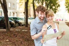 Couples de touristes dans la ville recherchant des directions sur la carte Image stock