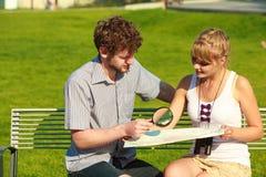 Couples de touristes dans la ville recherchant des directions sur la carte Photos stock