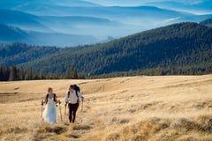Couples de touristes de mariage voyageant dans les montagnes Lune de miel aux Alpes Photographie stock