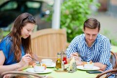 Couples de touristes de restaurant mangeant au café extérieur La jeune femme et son ami apprécient leur nourriture au temps de dé Photos libres de droits