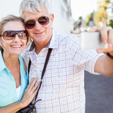 Couples de touristes heureux prenant un selfie dans la ville Photo stock