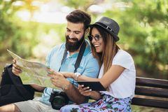 Couples de touristes heureux regardant la carte Photographie stock