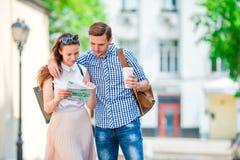 Couples de touristes heureux voyageant dans le sourire de l'Europe heureux Amis caucasiens avec la carte de ville à la recherche  Photographie stock libre de droits