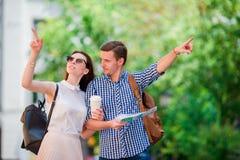 Couples de touristes heureux voyageant dans le sourire de l'Europe heureux Amis caucasiens avec la carte de ville à la recherche  Image stock