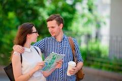 Couples de touristes heureux voyageant dans le sourire de l'Europe heureux Amis caucasiens avec la carte de ville à la recherche  Photo libre de droits