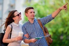 Couples de touristes heureux voyageant dans le sourire de l'Europe heureux Amis caucasiens avec la carte de ville à la recherche  Photos libres de droits