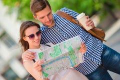 Couples de touristes heureux voyageant dans le sourire de l'Europe heureux Amis caucasiens avec la carte de ville à la recherche  Images stock
