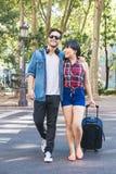 Couples de touristes marchant dans la ville avec la valise Images stock