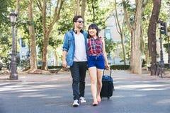 Couples de touristes marchant dans la ville avec la valise Images libres de droits