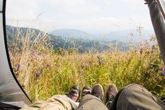 Couples de touristes se situant dans une tente appréciant le Mountain View merveilleux Photo libre de droits