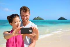 Couples de vacances de plage prenant le selfie sur le smartphone Image stock