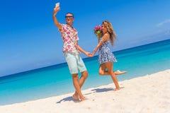 Couples de vacances sur la plage prenant des photos avec le téléphone d'appareil-photo Image stock