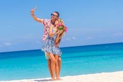 Couples de vacances sur la plage prenant des photos avec le téléphone d'appareil-photo Image libre de droits
