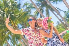 Couples de vacances sur la plage prenant des photos avec le téléphone d'appareil-photo Images libres de droits