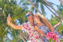 Couples de vacances sur la plage prenant des photos avec le téléphone d'appareil-photo roma Image stock