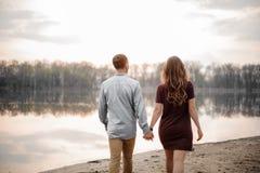 Couples de vue arrière dans l'amour marchant le long du bord de lac sur le fond des arbres Images stock