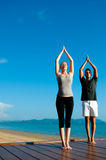 Couples de yoga par Ocean Photo stock