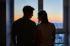 Couples de Yong dans l'amour se tenant près de la fenêtre pendant le lever de soleil, pousse moyenne de silhouette Images libres de droits