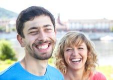 Couples de Youing dans des chemises colorées riant fort Images stock