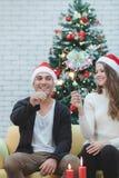 Couples de Youn dans le chapeau rouge se reposant sur le sofa entre les arbres de Noël a photos libres de droits
