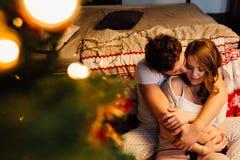 Couples dedans dans des pyjamas se reposant sur le plancher à côté du lit près de l'arbre de Noël Photos stock