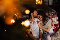 Couples dedans dans des pyjamas se reposant sur le plancher à côté du lit près de l'arbre de Noël Image libre de droits
