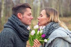 Couples dehors avec des fleurs s'embrassant photos libres de droits