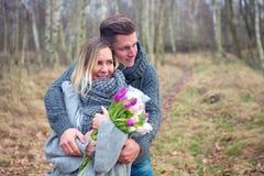 Couples dehors avec des fleurs s'embrassant photo stock