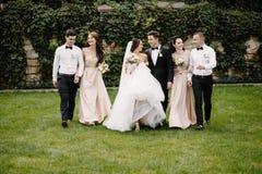 Couples, demoiselles d'honneur et garçons d'honneur de nouveaux mariés ayant l'amusement dehors Images stock