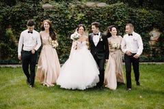 Couples, demoiselles d'honneur et garçons d'honneur de nouveaux mariés ayant l'amusement dehors Photos stock