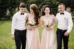 Couples, demoiselles d'honneur et garçons d'honneur de nouveaux mariés ayant l'amusement dehors Image stock