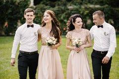 Couples, demoiselles d'honneur et garçons d'honneur de nouveaux mariés ayant l'amusement dehors Photos libres de droits