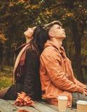 Couples derrière la table en bois en parc d'automne Photos libres de droits